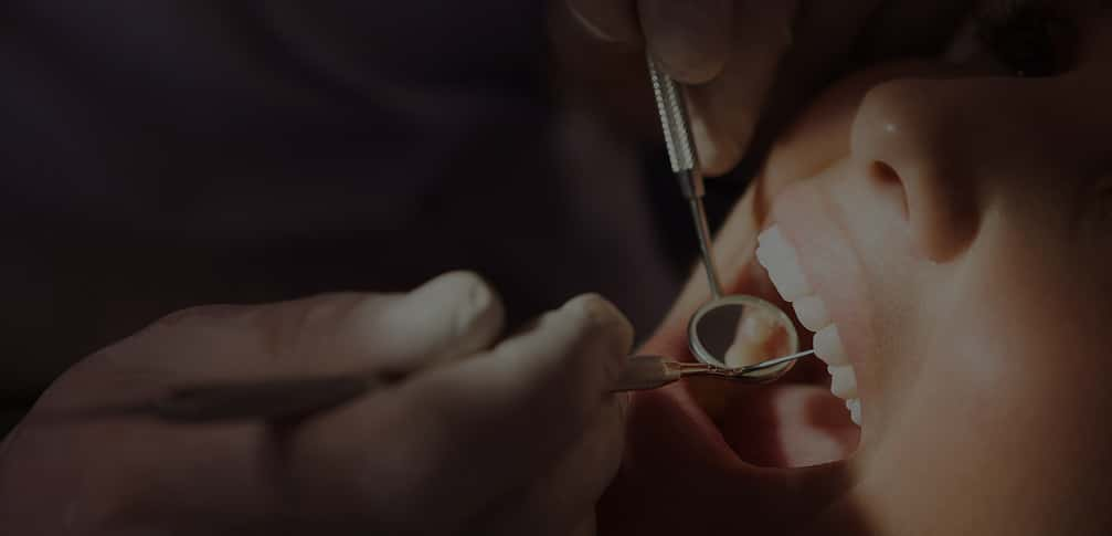 Dentist examining a patients teeth in the dentists chair under bright light at the dental clinic;